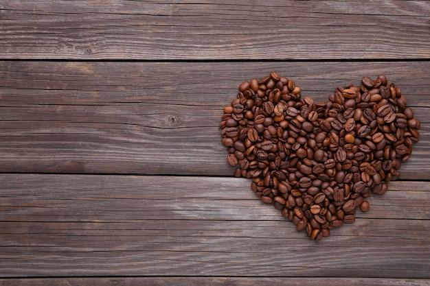 Grãos de café em forma de coração no fundo cinza