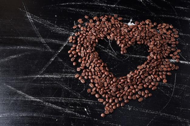 Grãos de café em forma de coração no preto