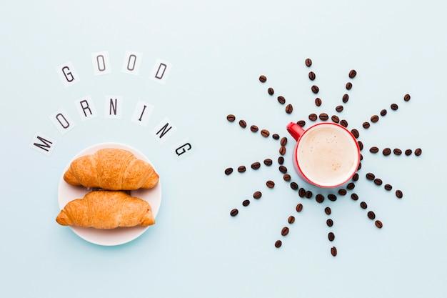 Grãos de café em forma de sol e croissants