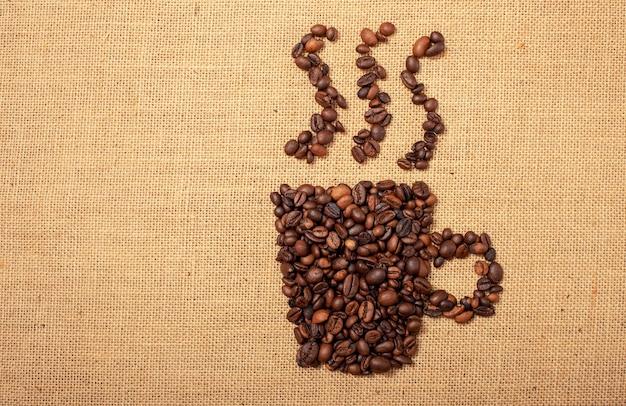Grãos de café em forma de xícara sobre um fundo de tecido de juta