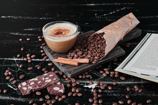 Grãos de café em fundo preto com bebida e biscoitos.