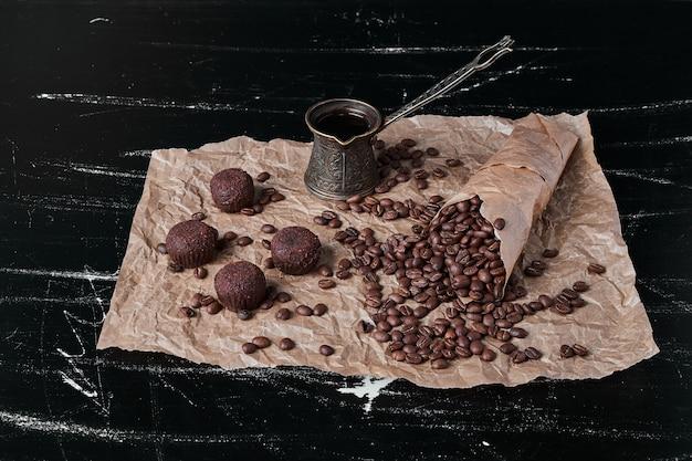 Grãos de café em fundo preto com bombons de chocolate.
