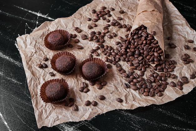 Grãos de café em fundo preto com bombons.
