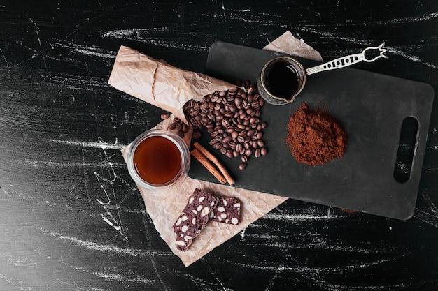 Grãos de café em fundo preto com pó.