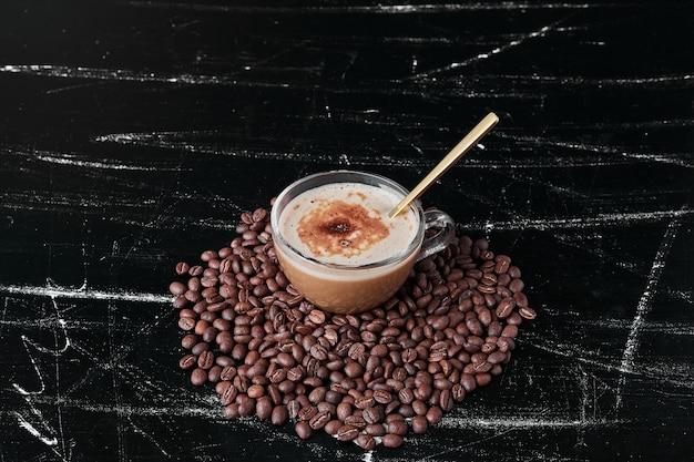 Grãos de café em fundo preto com um copo de bebida.