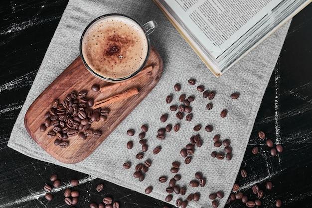 Grãos de café em fundo preto com uma xícara de bebida e canelas.