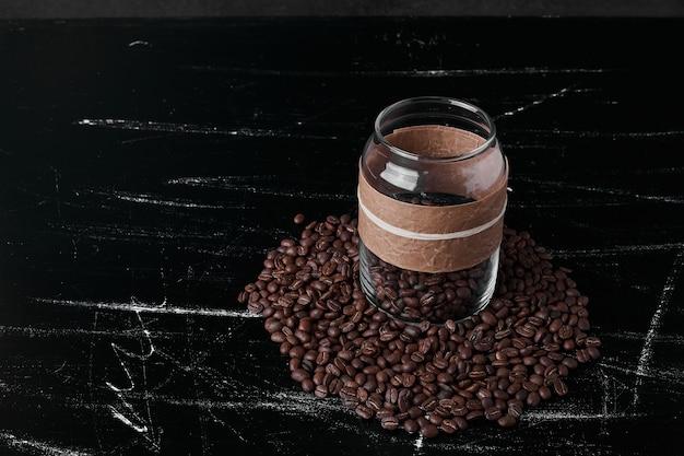 Grãos de café em fundo preto e na jarra de vidro.