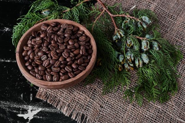 Grãos de café em fundo preto na xícara de madeira.