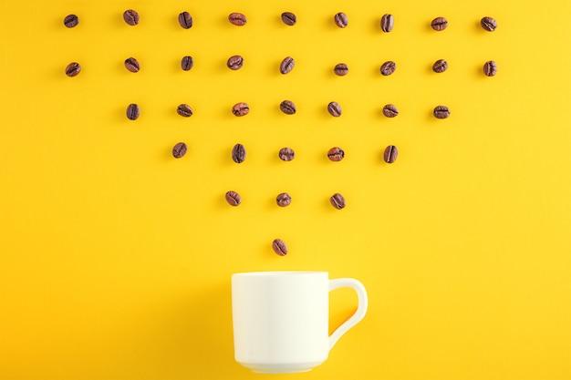 Grãos de café em linha e xícara de café sobre fundo amarelo