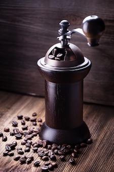 Grãos de café em moedor de café na madeira