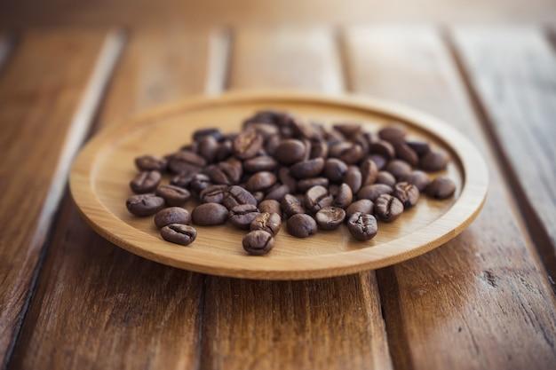 Grãos de café em pires de madeira sobre a mesa