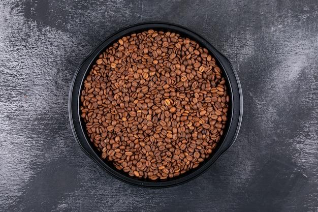 Grãos de café em pote preto na vista superior da superfície escura
