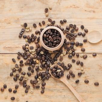 Grãos de café em recipiente de madeira e na mesa com colher