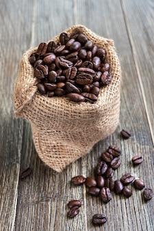 Grãos de café em saco de saco em um fundo de madeira. visão vertical