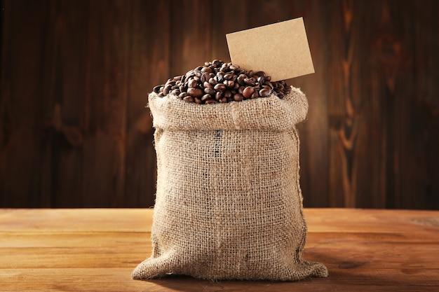 Grãos de café em saco na mesa