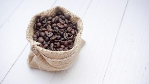 Grãos de café em saco no chão de madeira branco