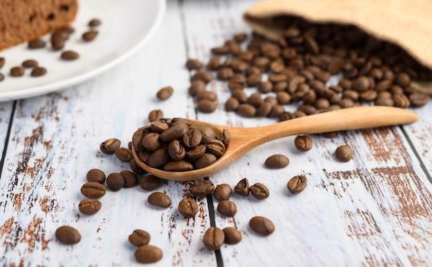 Grãos de café em sacos de colher e cânhamo de madeira em uma mesa de madeira branca.