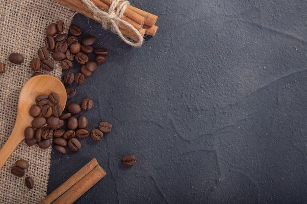 Grãos de café em tecido de serapilheira, colher de pau e canela na vista superior da superfície de concreto escuro