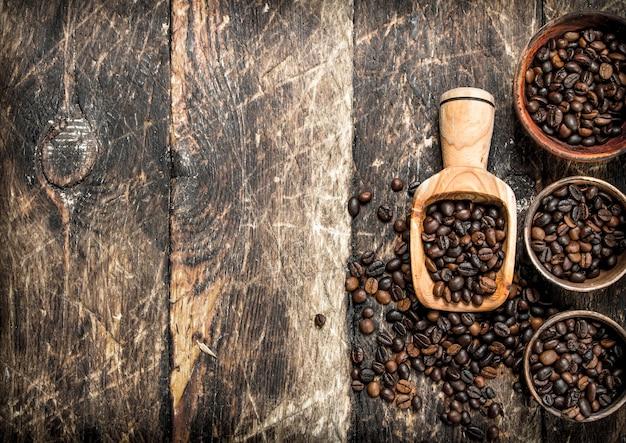 Grãos de café em tigelas. sobre um fundo de madeira.