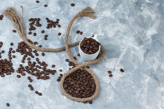 Grãos de café em um copo branco com uma corda lisa sobre um fundo de gesso cinza