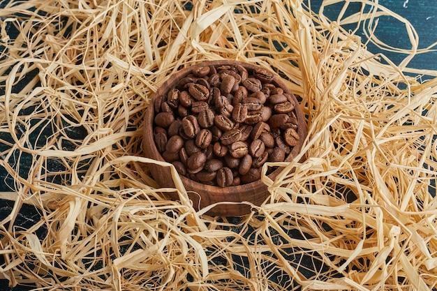 Grãos de café em um copo de madeira na grama seca.
