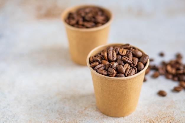 Grãos de café em um copo de papel grãos torrados servindo arábica ou robusta