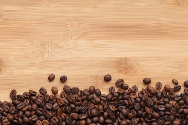 Grãos de café em um fundo de madeira de cima com copyspace