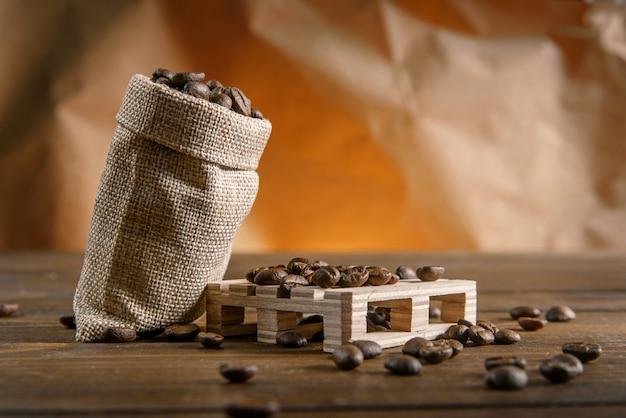Grãos de café em um pequeno saco em uma mesa de madeira