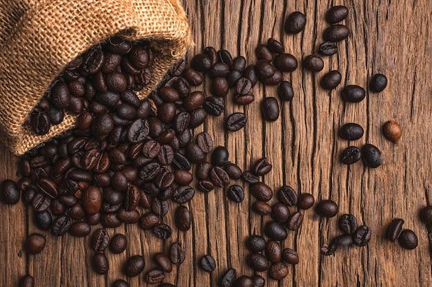 Grãos de café em um saco em fundo de madeira velho