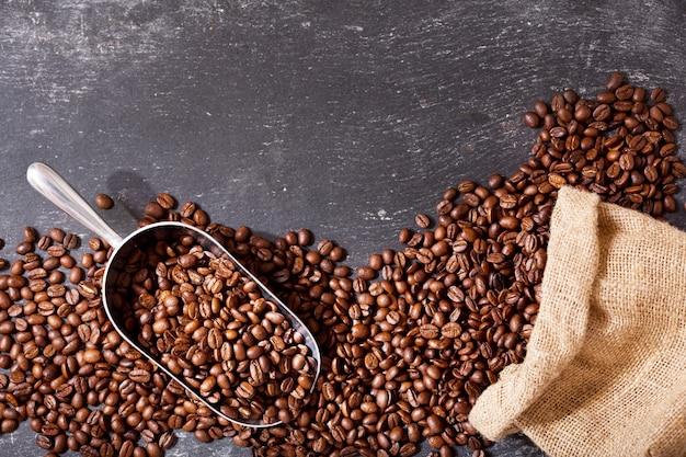 Grãos de café em um saco em fundo escuro, vista superior