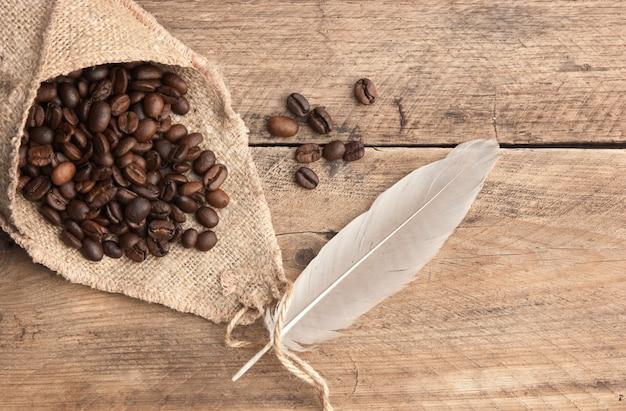 Grãos de café em um saco em um fundo de madeira