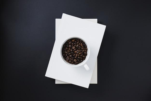 Grãos de café em uma caneca de café branca colocada em livros brancos empilhados sobre um fundo preto