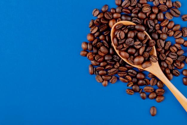 Grãos de café em uma colher de pau em grãos de café na vista superior de fundo azul