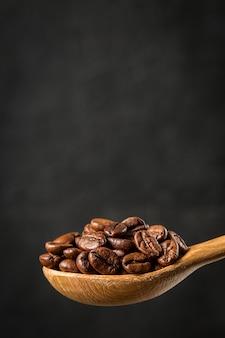 Grãos de café em uma colher de pau no fundo cinza