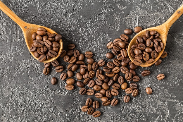 Grãos de café em uma colher de pau no fundo de pedra