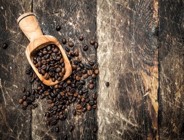 Grãos de café em uma colher. sobre um fundo de madeira.