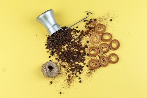Grãos de café em uma jarra com bolos de arroz, cordas e pãezinhos planos sobre um fundo amarelo