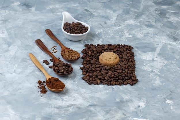 Grãos de café em uma jarra de porcelana branca com grãos de café, café instantâneo, farinha de café em colheres de madeira, vista de alto ângulo sobre um fundo de mármore azul claro