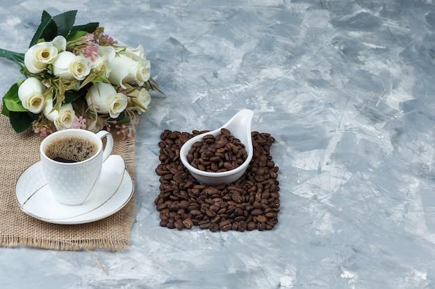 Grãos de café em uma jarra de porcelana branca com uma xícara de café, um pedaço de saco, uma visão de alto ângulo de flores sobre um fundo de mármore azul