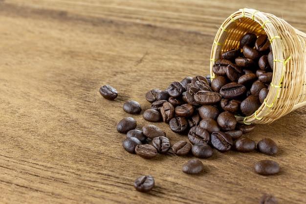 Grãos de café em uma pequena cesta de bambu na mesa de madeira