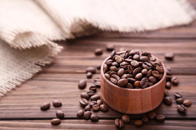 Grãos de café em uma tigela de madeira com pano de saco em brown