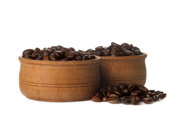Grãos de café em uma tigela de madeira em um fundo branco e isolado. grãos de café torrados