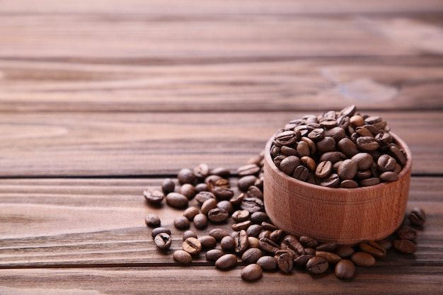 Grãos de café em uma tigela de madeira marrom