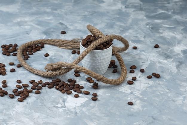 Grãos de café em uma xícara branca com vista de alto ângulo de corda em um fundo de gesso cinza