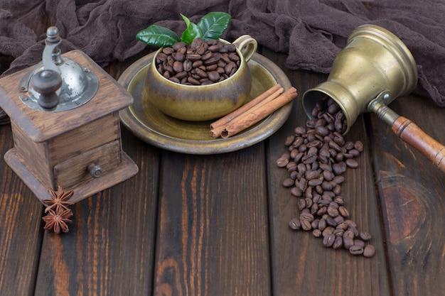 Grãos de café em uma xícara, cafeteira, canela e velho moedor de café manual em uma mesa de madeira