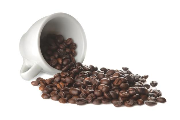 Grãos de café em uma xícara de café branco sobre um fundo branco e isolado. grãos de café torrados
