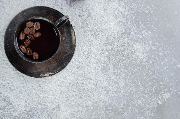 Grãos de café em uma xícara de café com pó de coco na mesa de mármore.