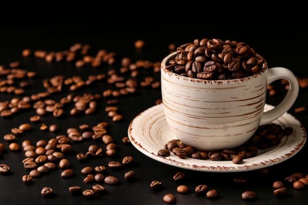 Grãos de café em uma xícara de luz sobre um fundo escuro com grãos de café espalhados em cima da mesa