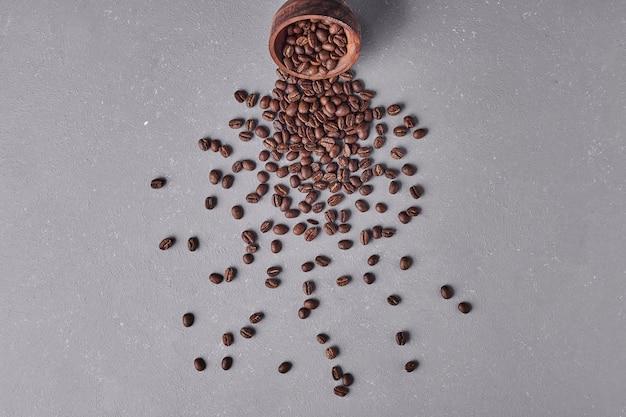 Grãos de café em uma xícara de madeira.