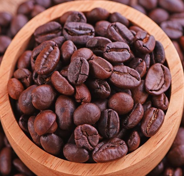 Grãos de café em uma xícara de madeira